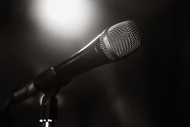 Zwart-wit beeld van de microfoon. de microfoon op het podium is van dichtbij. een cafe. bar. een restaurant. klassieke muziek. muziek