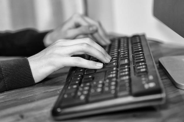 Zwart-wit beeld van een bedrijf handen werken en typen op laptop toetsenbord in office