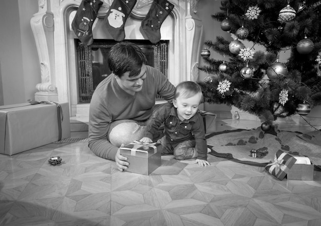 Zwart-wit beeld van een jonge vader die speelt met zijn 1-jarige babyjongen op de vloer naast de kerstboom