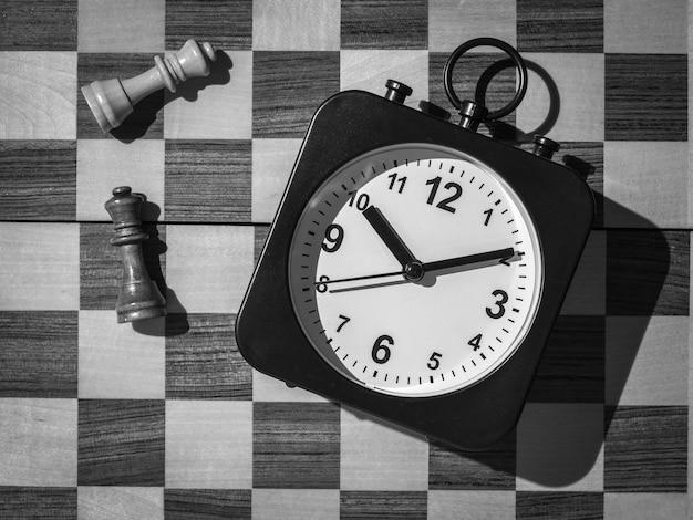 Zwart-wit beeld van een klok op de achtergrond van een schaakbord en schaakstukken. het concept van zaken en tijd.