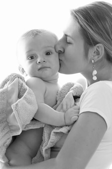 Zwart-wit beeld van een mooie jonge moeder die haar babyjongen kuste, bedekt met een handdoek na het baden