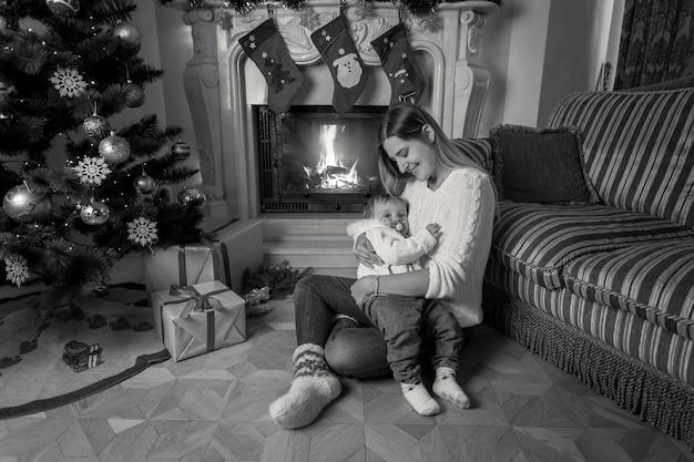 Zwart-wit beeld van een mooie jonge moeder die met haar zoontje naast de open haard zit met kerstmis