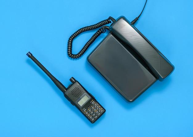 Zwart-wit beeld van een walkie-talkie en telefoon op een blauwe achtergrond.