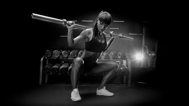 Zwart-wit beeld van fit jonge vrouw in geweldige vorm tillen