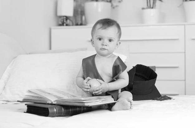 Zwart-wit beeld van grappige baby met afstudeerpet en lint die groot boek leest