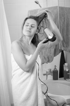 Zwart-wit beeld van jonge vrouw binnen met haardroger bij badkamerspiegel