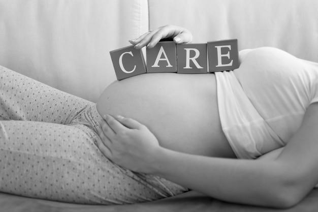Zwart-wit beeld van letters op houten blokken die woordzorg maken op de buik van zwangere vrouwen