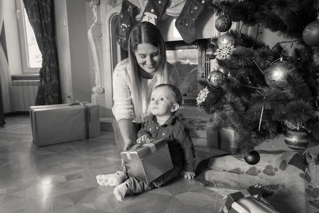Zwart-wit beeld van moeder en baby met kerstcadeaus op de vloer in de woonkamer