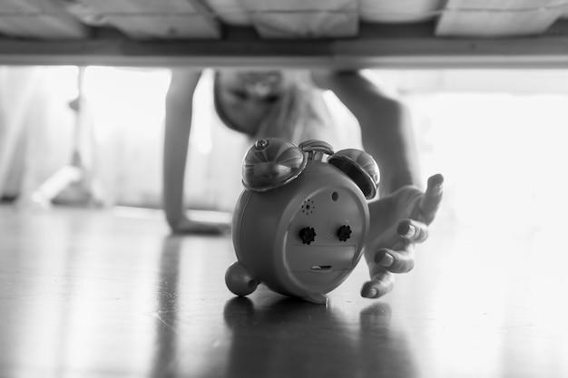 Zwart-wit beeld van mooi meisje dat naar een wekker onder het bed reikt