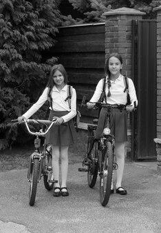 Zwart-wit beeld van twee lachende meisjes in schooluniform met fietsen voor het huis