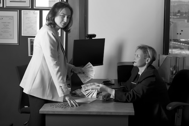 Zwart-wit beeld van twee russische zakenvrouwen in pakken die israëlische bankbiljetten en amerikaans dollargeld uitwisselen in modern office. zaken, financiën, valutafondsen. vrouwelijke hand met bankbiljetten