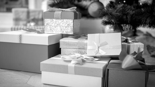 Zwart-wit beeld van veel geschenken en cadeautjes in dozen die zijn vastgebonden met linten die op de vloer onder de kerstboom liggen