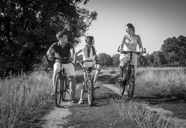 Zwart-wit beeld van vrolijke jonge familie rijden op fietsen op weide