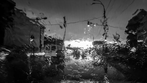 Zwart-wit beeld van waterdruppels die tijdens het regenen op de voorruit van de auto stromen. natte autovoorruit