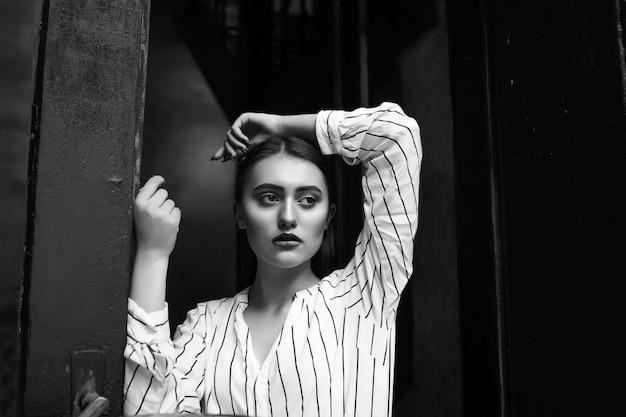 Zwart-wit binnenportret van een droevige, verbluffende jonge vrouw draagt een gestreept wit overhemd