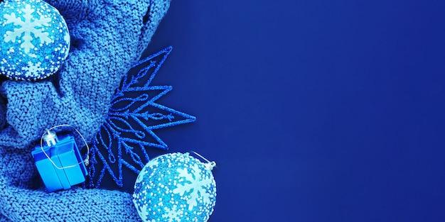 Zwart-wit blauwe banner: gebreide stof, kerstmisspeelgoed en een glanzende kerstster op een blauwe achtergrond. platte lay-out, bovenaanzicht, ruimte voor kopiëren.