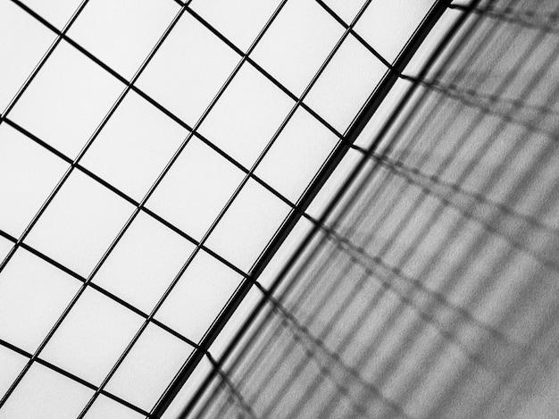 Zwart-wit bovenaanzicht van een metalen rooster gietende schaduwen