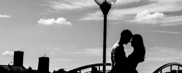 Zwart-wit donker silhouet van paar op de achtergrond van de grote stad. man en vrouw knuffelen in de buurt van de lantaarn.