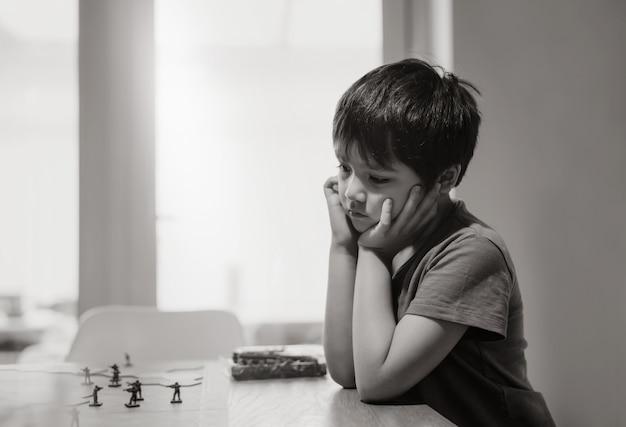 Zwart-wit emotioneel portret van trieste jongen die alleen zit en speelt met tankspeelgoed