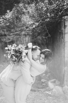 Zwart-wit foto gelukkig lachend bruidegom hugs bruid in een mooie jurk bruid houdt in haar handen een
