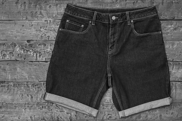 Zwart-wit foto van denim shorts op houten tafel. modieuze unisex-kleding. zomer denim kleding.