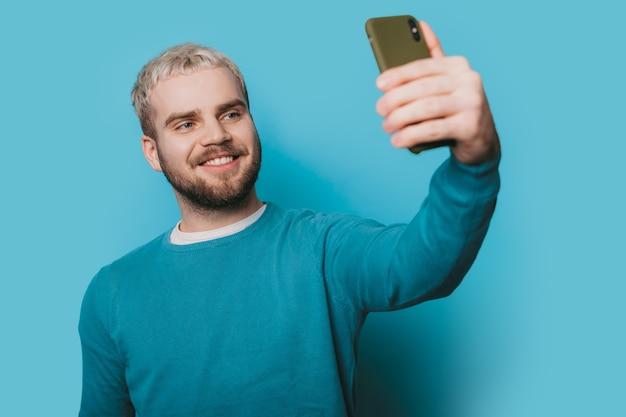 Zwart-wit foto van een blanke man met blond haar en baard die een selfie maakt met een telefoon op een blauwe muur