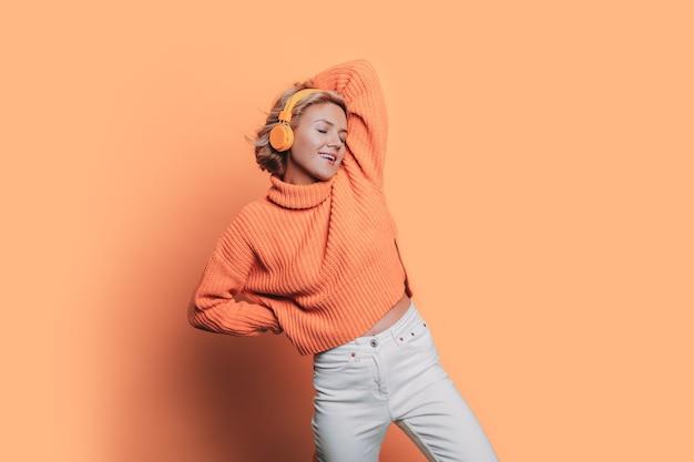 Zwart-wit foto van een blanke vrouw die naar muziek luistert op een koptelefoon die zich voordeed op een oranje muur