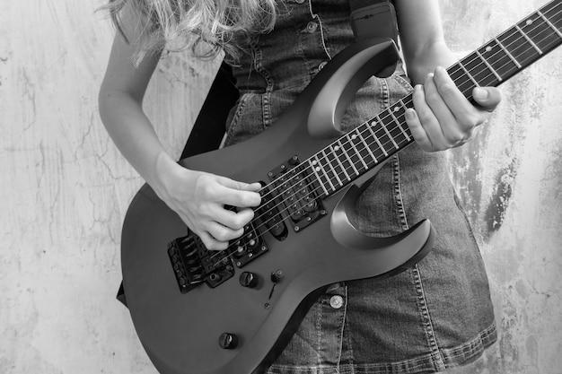 Zwart-wit foto van een meisje dat de elektrische gitaar speelt.