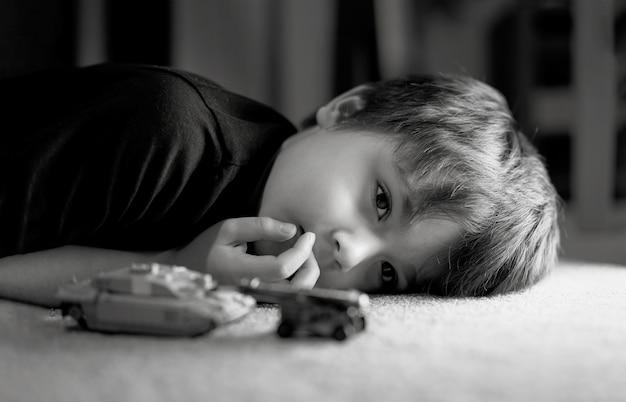 Zwart-wit foto van eenzame jongen die op vloer bepaalt die uit diep in gedachten kijkt