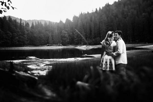 Zwart-wit foto van kussen pasgetrouwden die in hoog gras voor bergmeer staan