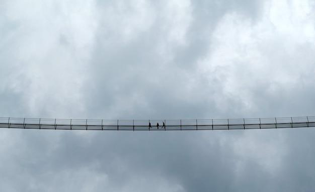 Zwart-wit foto van mensen op een hoge hangbrug bewolkte hemel lechtal oostenrijk lech