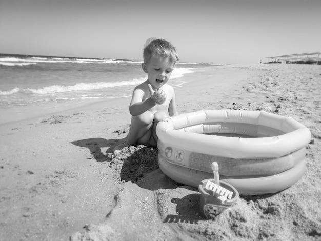 Zwart-wit foto van peuter jongen spelen op het strand van de zee met opblaasbaar zwembad. kind ontspannen en plezier hebben tijdens de zomervakantie vakantie.
