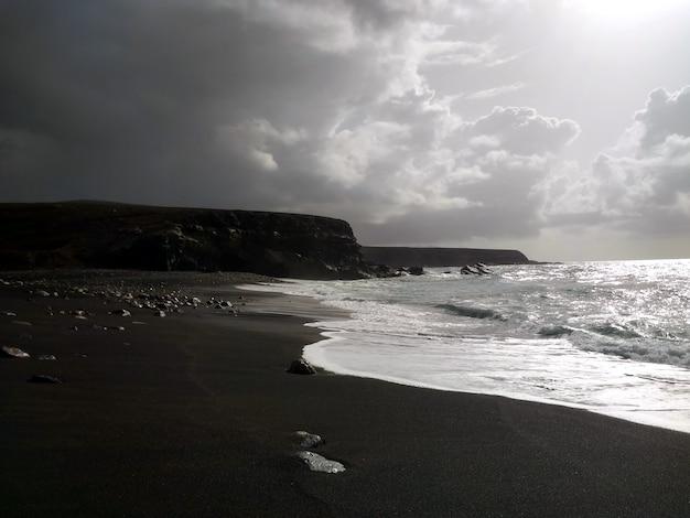Zwart-wit foto van rustige golven aan de kustlijn