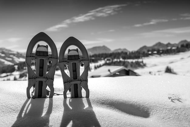 Zwart-wit foto van twee sneeuwschoenen begraven in de sneeuw met de besneeuwde bergen