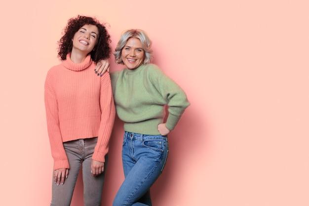 Zwart-wit foto van twee vrouwen met krullend haar die zich voordeed op een studiomuur met vrije ruimte glimlachend in de camera