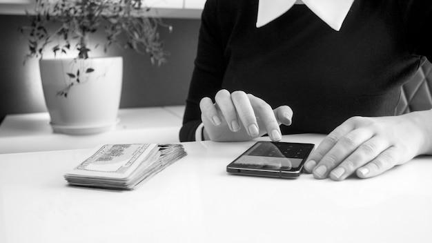 Zwart-wit foto van vrouwelijke zakenvrouw die geld munt met behulp van rekenmachine op smartphone,