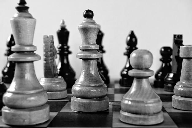 Zwart-wit houten schaakstukken prachtig gefotografeerd, monochrome indoor speelachtergrond.