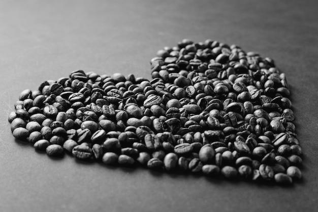 Zwart-wit koffiebonen in de vorm van een hart geïsoleerd op een grijze textuur achtergrond voor design. saint valentine's day-kaart op 14 februari, vakantieconcept.