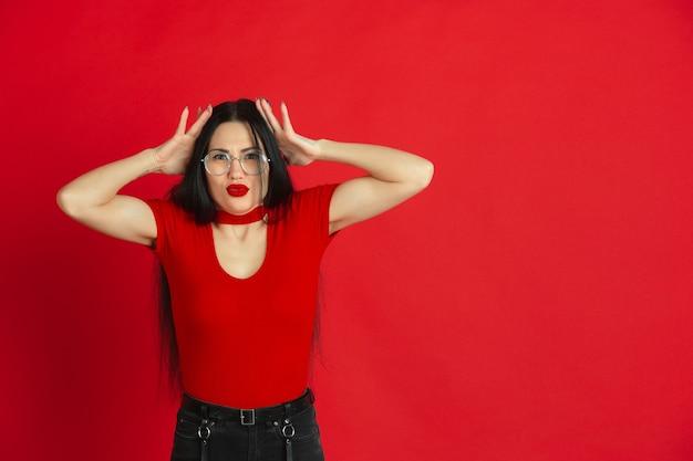Zwart-wit portret van blanke jonge vrouw op rode muur, emotioneel en expressief express