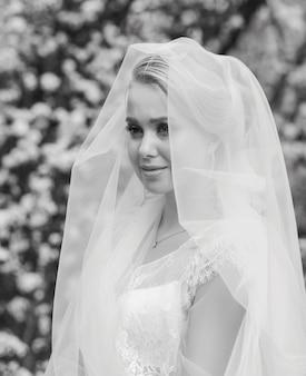 Zwart-wit portret van de bruid met een sluier die op de bruidegom wacht