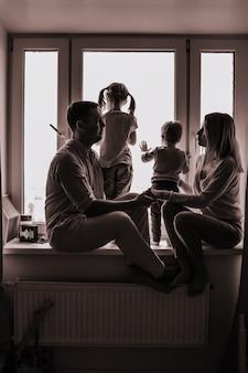 Zwart-wit portret van een blanke familie die uit het raam kijkt