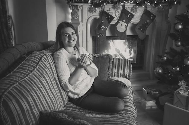 Zwart-wit portret van een gelukkig lachende vrouw die thee drinkt op de bank bij de open haard, versierd voor kerstmis