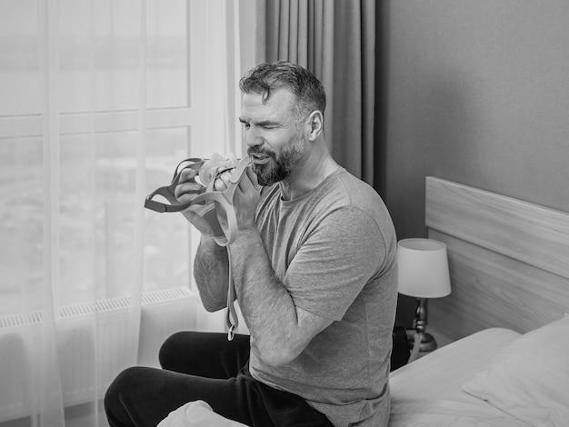 Zwart-wit portret van een gelukkig uitgeruste man met chronische ademhalingsproblemen na het gebruik van een cpap-machine
