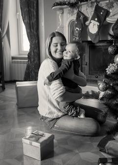 Zwart-wit portret van een gelukkige jonge moeder die haar 1-jarige babyjongen knuffelt bij de kerstboom