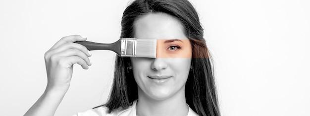 Zwart-wit portret van een jonge vrouw die haar oog schildert met een penseel