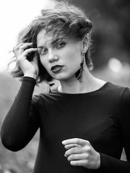 Zwart-wit portret van een jonge vrouw met lang erachter haar en zonlicht