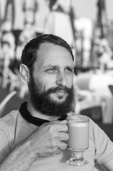 Zwart-wit portret van een knappe, bebaarde man die hete koffie drinkt, 's ochtends espressokoffie met melk kijkt in de verte in zonsondergangverlichting. concept met ruimte voor tekst. man met een koffiemok