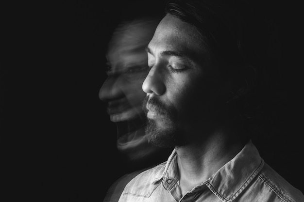 Zwart-wit portret van een man met zijn ogen dicht en zelf wazig schreeuwend geestesziekte