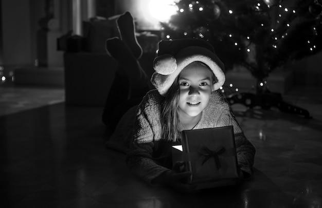 Zwart-wit portret van een schattig lachend meisje dat met een kerstcadeaudoos op de vloer naast de open haard ligt