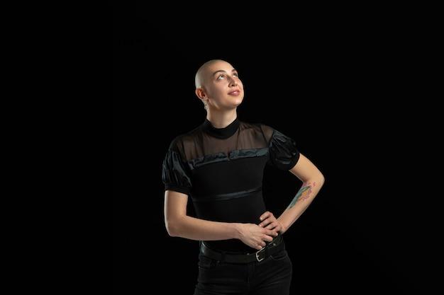 Zwart-wit portret van jonge kale vrouw op zwarte muur
